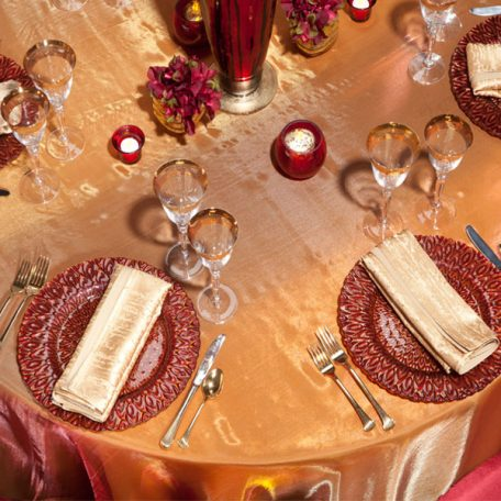 Blaze Sheer Table Overlay shown over a Gold Twill Table Linen. A gold Contour Napkin on top of our Red/Gold Peacock Glass Charger