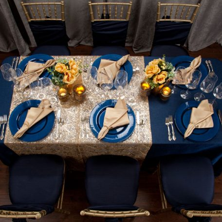 Blue Cotier Table Linen with Golden Helena Table Runner, Goldmine Matte Satin Napkins and Blue Lino Limoges Glass Chargers