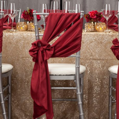 Golden Helena Beaded overlay shown over an ivory Shantung Table Linen. Topped off with our Ice Square with Gold Rim Charger and a Merlot Shantung Napkin