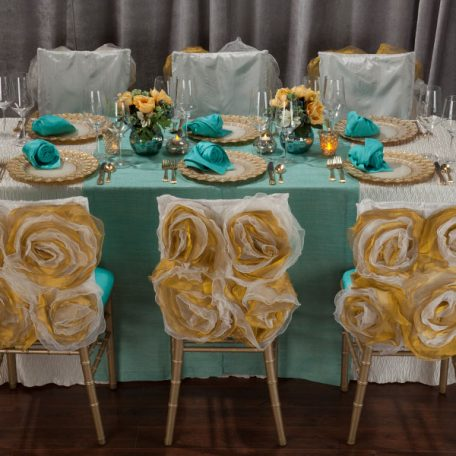Ivory Rhythm Table Linen with on Gables Table Runner and a Lagoon Shantung napkin on an Ivory Florence Glass Charger